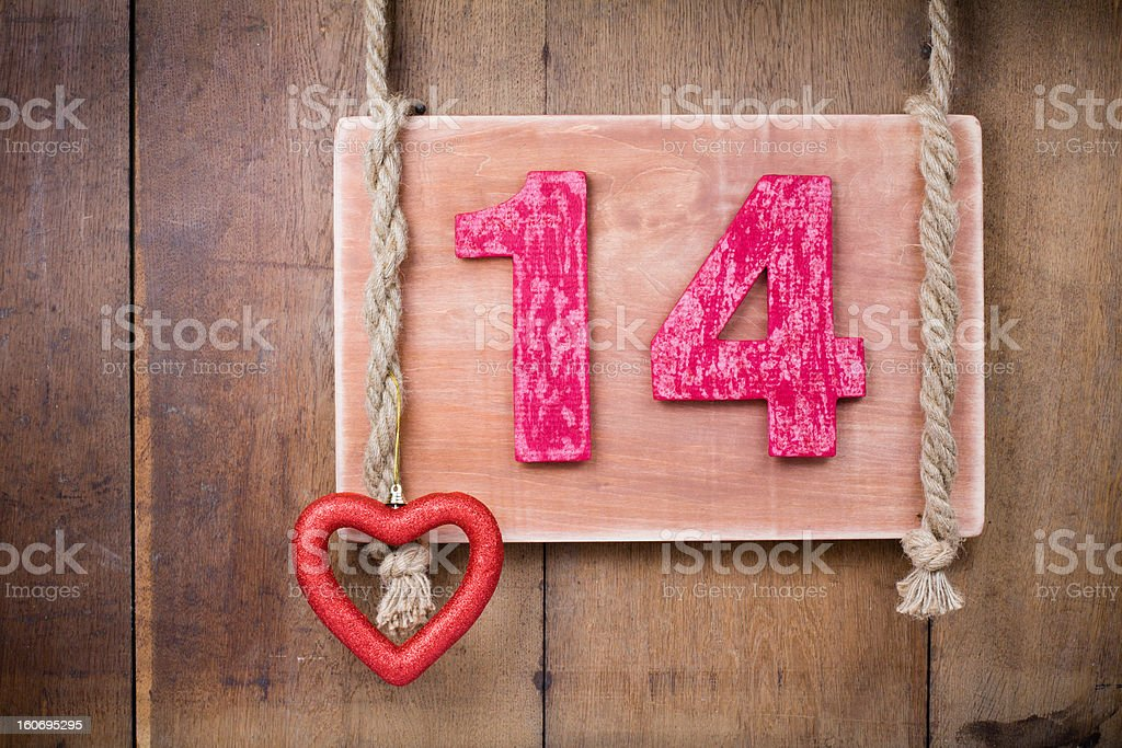 Valentine heart shape, number fourteen hanging on wooden planks background royalty-free stock photo