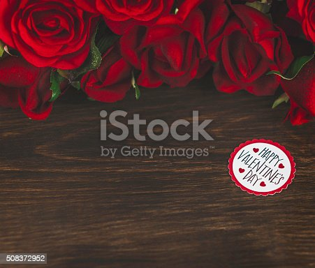 Valentine red rose bouquet on rustic wooden table with message. Getty Images Valentine's Brief 603393001