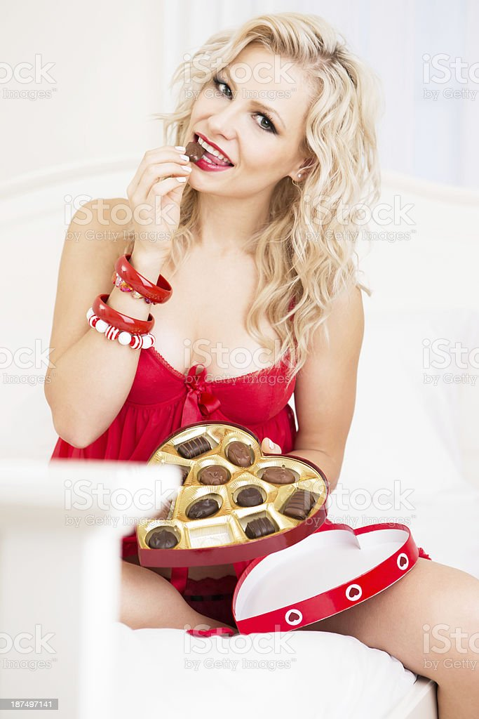 Valentine- Woman in red lingerie eating chocolate - Stock image .