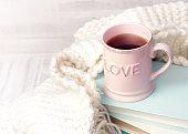 Valentine's background. Coffee tea mug books knits on wood.