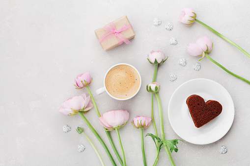 Breakfast for Valentines day with cup of coffee, gift, flowers and cake in shape of heart on gray table from above in flatlay style.