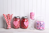 Valentines Day candy in a variety of glass containers on white wood.