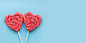 Valentine's card. Two lollipops candy as heart on blue background. Funny concept. Space for text.