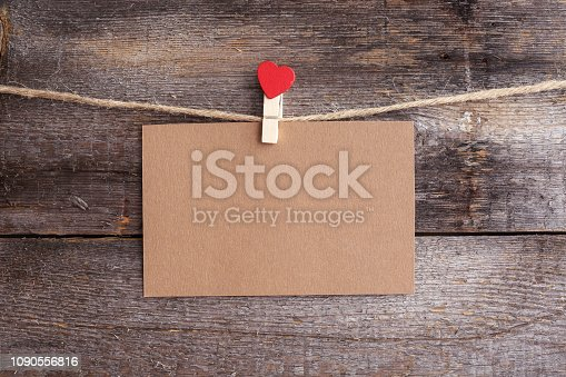 Valentines day card hanging on pin with heart on rope over wooden background, copy space for text