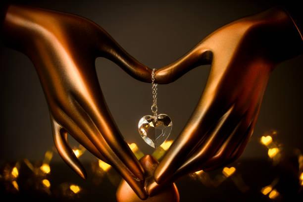 zum valentinstag: eine herzform bestehend aus händen und ein kristallherz auf einem dunklen hintergrund. der ort für - einladungskarten kostenlos stock-fotos und bilder