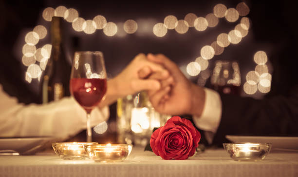 Valentines day. Anniversary. Couple holding hands having a romantic dinner date. table for two stock pictures, royalty-free photos & images
