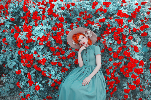 Valentines Day background. Cute retro girl with red lips in mint dress on a beautiful summer background. Fashionable clothes. Valentines Day cute redhead model in hat on background of bush of roses.