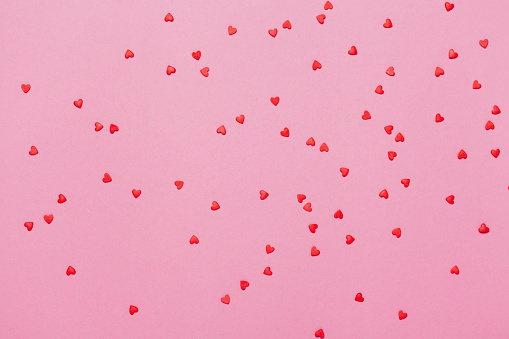 Valentine's day background. Little red hearts on pink background.