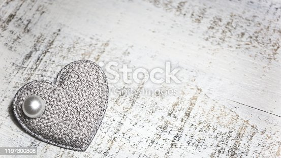 Fabric heart with a pearl on a white wooden background. Valentines day concept. Empty space for text on right side.