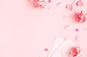 istock Valentine's Day background. Pink flowers, envelope, hearts on pastel pink background. Valentines day concept. Flat lay, top view, copy space 1199450923