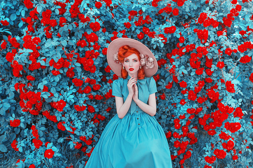 Valentines Day background. Spring rose flower garden. Fabulous lady with red lips in dress. Gardening on farm. Awesome flower wall. Redhead lady on fabulous background of rose garden. Spring gardening