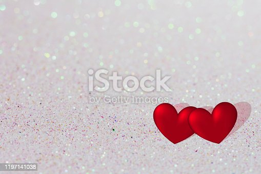 896306118istockphoto valentines day background, two red hearts on shiny bright background with copy space, valentine card 1197141038