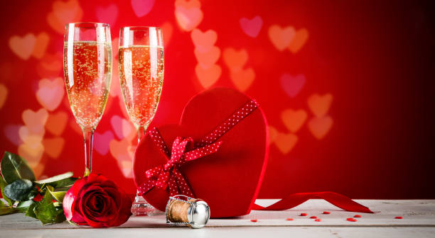 Valentines day background with champagne Background of Valentines day celebration with champagne, rose, heart shaped present and red candies. table for two stock pictures, royalty-free photos & images