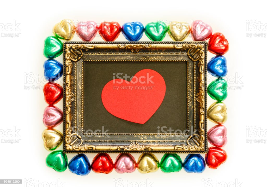Valentines Day background with colorful chocolates heart shape and gold frame from top view. Copy space royalty-free stock photo