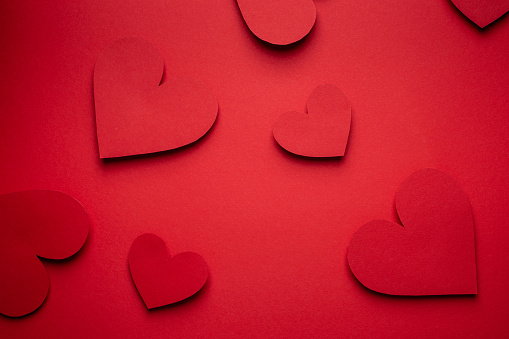 Red hearts cut from paper on red background, paper craft origami style, from above. Romantic Valentine's day red monochrome background, love concept. Different size hearts top view, paper art design