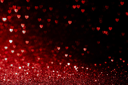Photo of valentines day background with red hearts glitter bokeh on black, card for Valentine's day, christmas and wedding celebration, Love bokeh shiny confetti textured template