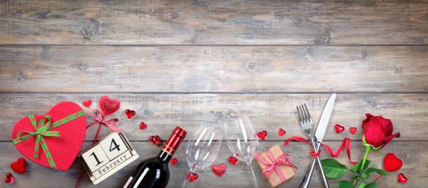 valentinstag-banner - gläser, flaschen und geschenk auf holzbrett - valentinstag stock-fotos und bilder