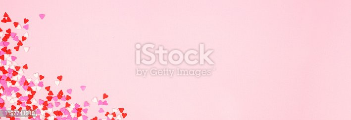 istock Valentines Day banner with corner border of candy heart sprinkles over a pink background with copy space 1197741218