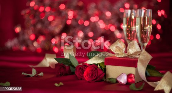 Valentine's Day Banner with Red Roses, Gift and Champagne on a Defocused Bokeh Lights Background