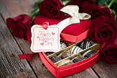 Valentine's day box of chocolates and red roses on a wood background.