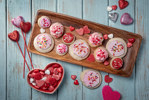 Valentines Day Candy Cupcakes Cookies and Decorations for a Party on Retro Blue Wood Background