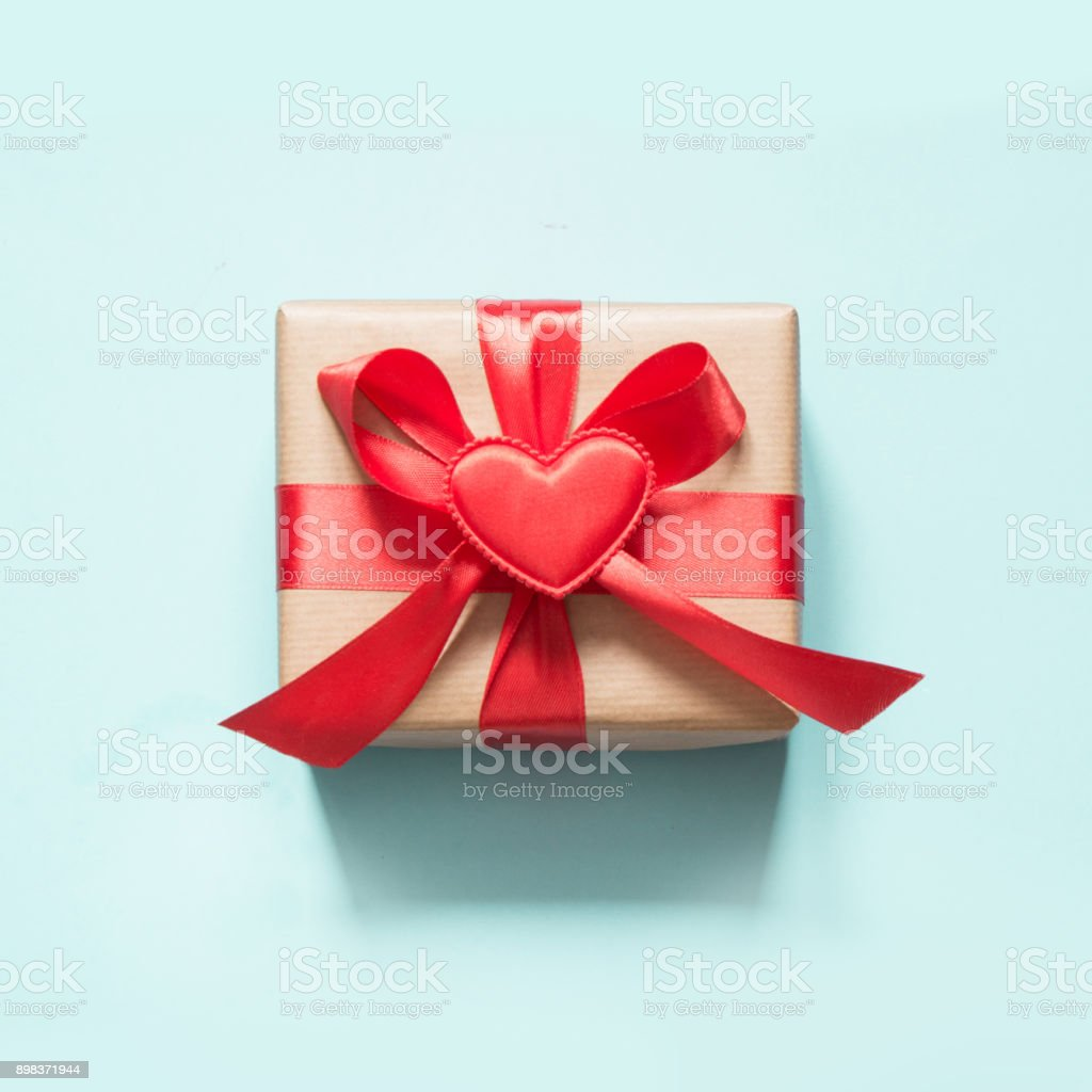 Valentine's day card. Gift with red ribbon and heart on blue surface. Top view. Square. stock photo