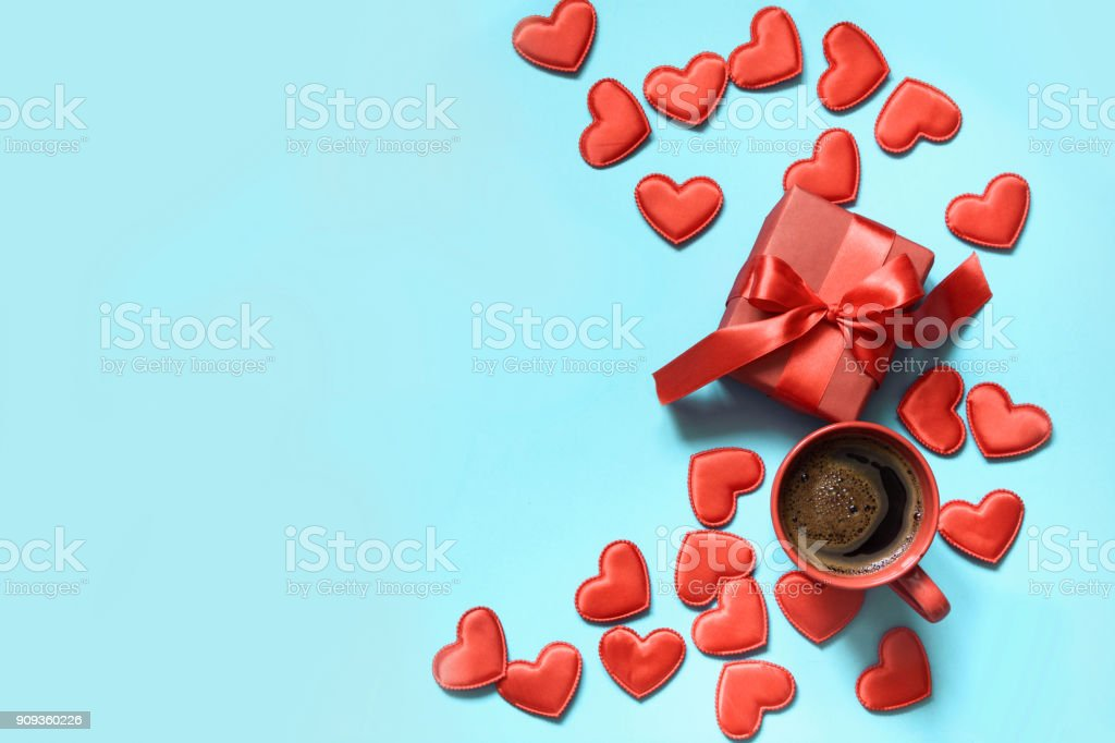 Valentine's day card. Gift with red ribbon, cup of coffee and hearts on blue. Top view. Copy space. stock photo