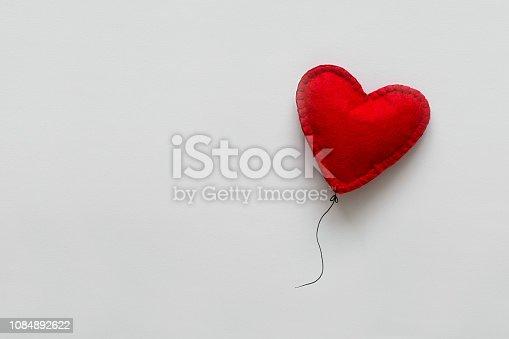 1078237178 istock photo Valentines day card. Red felt heart shape balloon on thread. Minimalist concept 1084892622