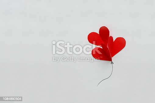 1078237178 istock photo Valentines day card. Red paper heart shape balloons on thread. Paper cut style and minimalist concept 1084892504