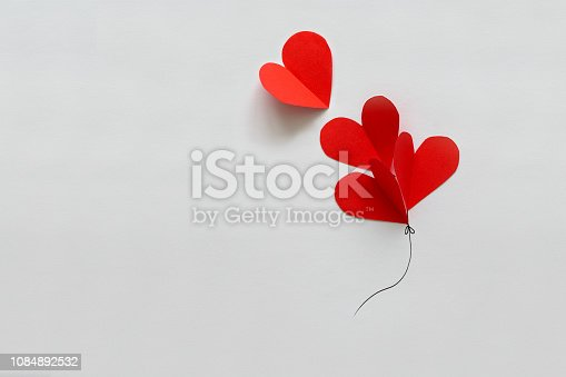 1078237178 istock photo Valentines day card. Red paper heart shape balloons on thread. Paper cut style and minimalist concept 1084892532