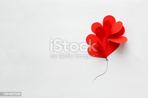 1078237178 istock photo Valentines day card. Red paper heart shape balloons on thread. Paper cut style and minimalist concept 1084892538