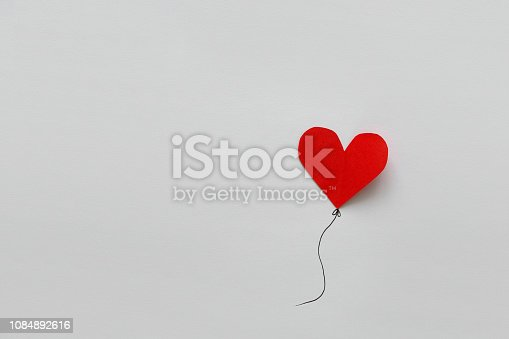 1078237178 istock photo Valentines day card. Red paper heart shape balloons on thread. Paper cut style and minimalist concept 1084892616