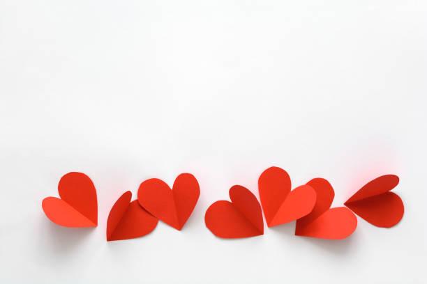 kartka walentynkowa. czerwone papierowe serca na białym papierze. styl cięcia papieru i minimalistyczna koncepcja - kartka na walentynki zdjęcia i obrazy z banku zdjęć