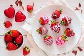 Valentines Day chocolate dipped strawberries. Above view table scene over a white wood background. Love and heart theme.