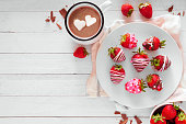 Valentines Day chocolate dipped strawberries. Top view table scene against a white wood background. Love and heart theme.