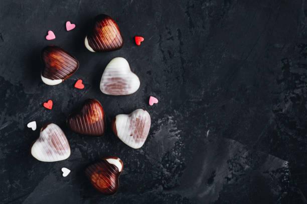 Valentinstag Schokoladenherzen auf dem dunklen Hintergrund. Dunkle, Milch und weiße Schokoladenherzen für Valentinstag. – Foto