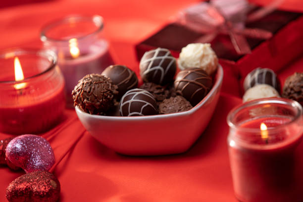 Valentines Day Chocolate Truffles Gift and Lighting Decorations on Silk Red Background stock photo