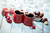 Valentines Day Coffee Cups Pair and Lighting Decorations on Light Blue Retro Wood Background