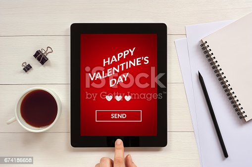 898149690 istock photo Valentine's day concept on tablet screen with office objects 674186658
