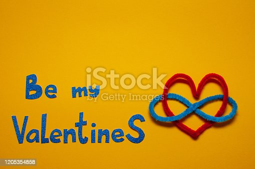 Valentine's Day concept, polyamory symbol, red heart, sign of infinity on a yellow background. Flat Lay.