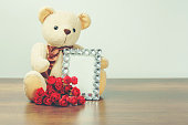 Valentine's day concept : Teddy bear hugging diamond frame and roses
