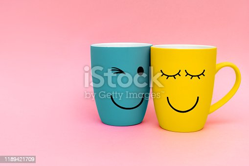 Valentine's day concept. Two happy cups yellow and turquoise colors on pink background. Happy friday word concept. Simbol of love and relationship. Copy space.