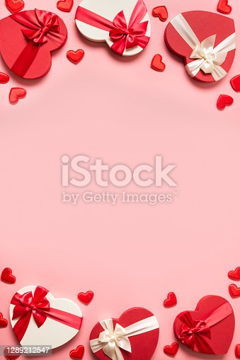 Valentine's Day romantic frame of gifts with red hearts on pink background. Flat lay. Vertical greeting card with copy space.