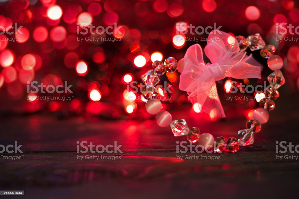valentines day consept backgroundcrystal heart with bow on background of red bokeh lights royalty