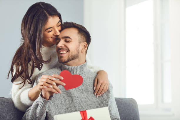 Valentine's day. Couple gives heart to the Valentine's Day in the room. stock photo