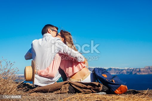 Valentine's day. Couple in love enjoying sea landscape on honeymoon on Santorini island, Greece. Man and woman kissing. Vacation and traveling