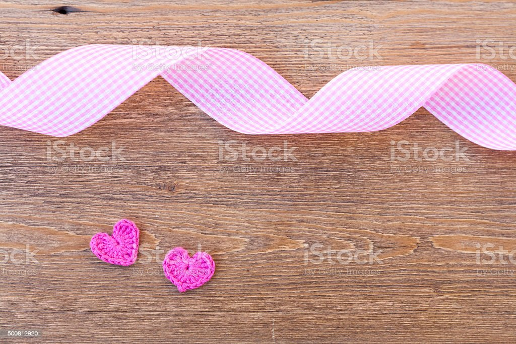 Valentines day crochet hearts and ribbon on wooden table royalty-free stock photo