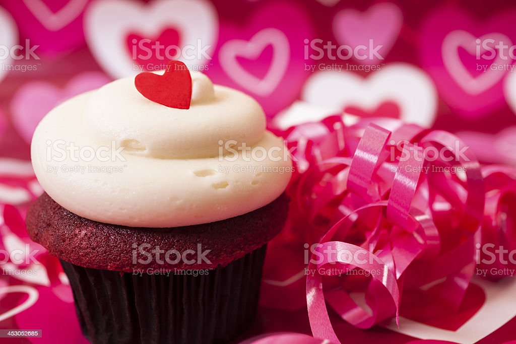 Valentine's Day: Cupcake with red heart on top.  Ribbon decorations. royalty-free stock photo