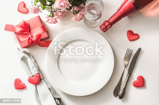istock Valentines day dinner with table place setting with red gift, glass for champagne, a bottle of champagne, pink roses, heart ornaments with silverware on white background. Top view. Valentine's card. 906514506