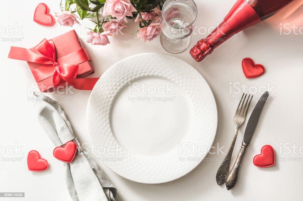 Jantar de dia dos namorados com tabela de ajuste de lugar com vermelho presente, copo de champanhe, uma garrafa de champagne, rosas, enfeites de coração com talheres de prata sobre fundo branco. Vista superior. Cartão do dia dos namorados. - foto de acervo